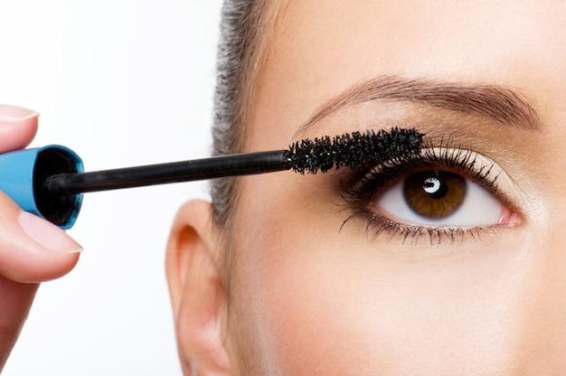 Vrouw mascara toe te passen op haar wimpers - macro-opname
