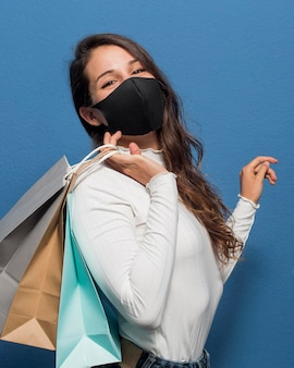 Vrouw masker dragen en boodschappentassen te houden
