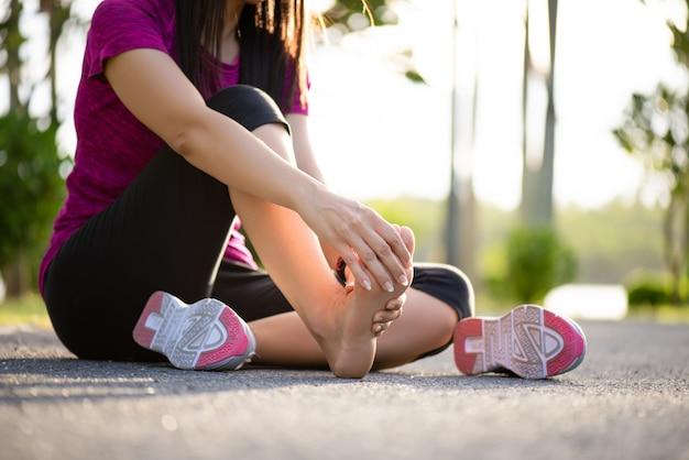 Vrouw masseert haar pijnlijke voet tijdens het sporten.