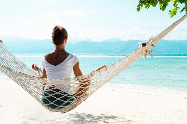 Vrouw mediteert op een schommel op het strand