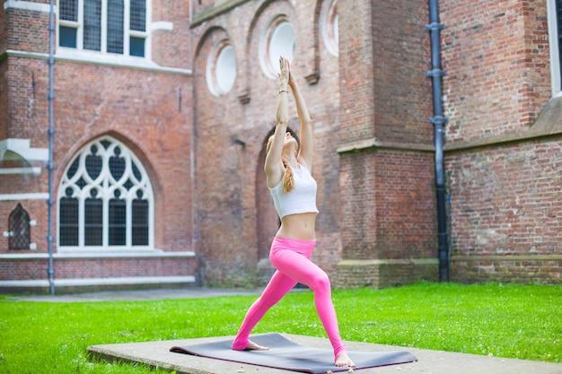 Vrouw mediteren en doen yoga sporters in stadsstraat