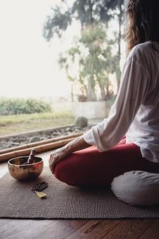 Vrouw mediteren. essentiële accessoires voor yoga en meditatie. kopieer ruimte