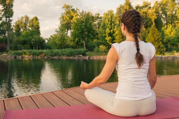 Vrouw mediteren in de buurt van meer