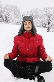 Vrouw mediteren in de winter in een besneeuwd park
