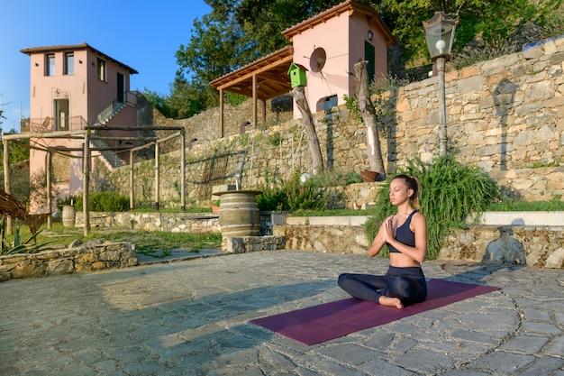 Vrouw mediteren in de yoga lotus houding zittend op een terras in de ochtendzon in de tuin