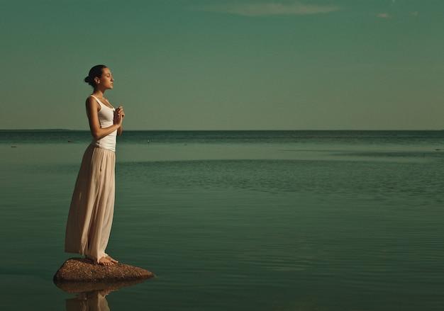 Vrouw mediteren in een yoga-pose op het strand bij zonsondergang