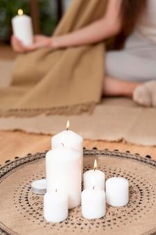 Vrouw mediteren met dienblad met kaarsen