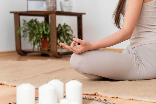 Vrouw mediteren met dienblad met kaarsen Gratis Foto
