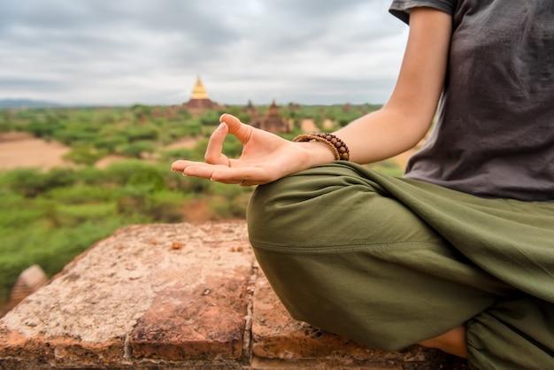 Vrouw mediteren op de top van pagode bij zonsondergang