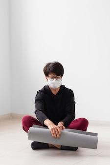 Vrouw mediteren terwijl ze een gezichtsmasker draagt