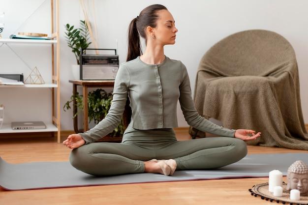 Vrouw mediteren thuis op de mat