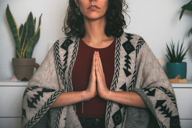 Vrouw mediterend met de palmen van de hand verbonden op de borst gekleed met een handgemaakte poncho