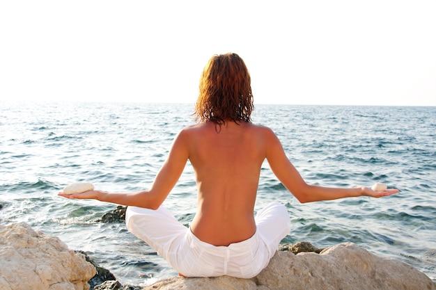 Vrouw mediterend met stenen tegen de zee