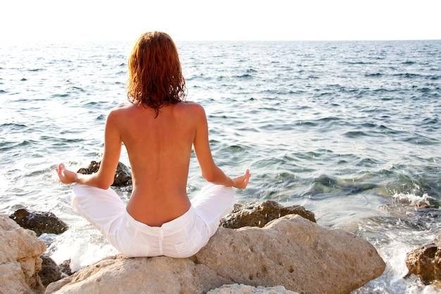 Vrouw mediterend tegen de zee