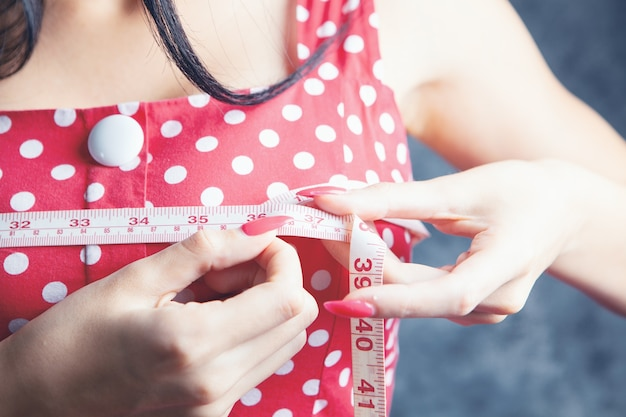 Vrouw meet haar borsten met een meetlint
