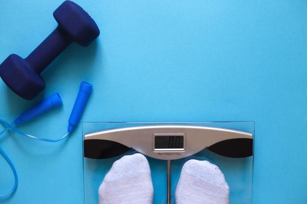Vrouw meet haar gewicht door met haar voeten op de weegschaal op een blauwe achtergrond te staan