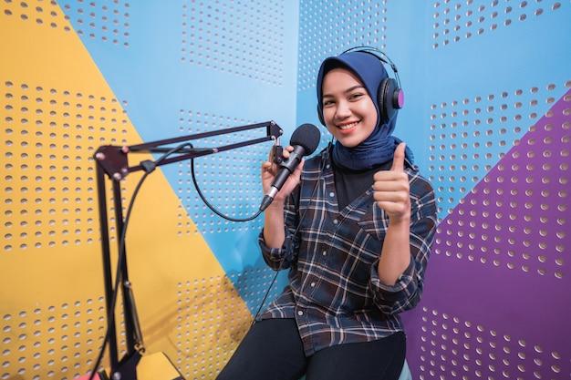 Vrouw meisje neemt een podcast op in haar studio duim omhoog
