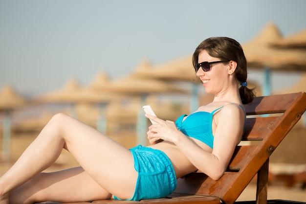 Vrouw messaging op mobiele telefoon op houten lounger