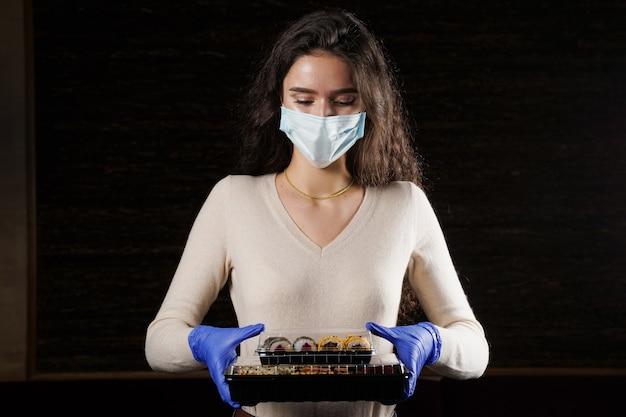 Vrouw met 2 sushidozen in handen met handschoenen en gezichtsmasker