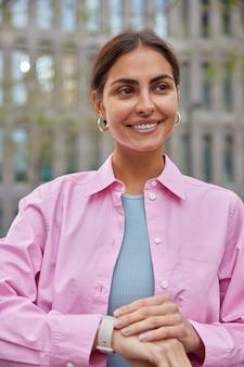 Vrouw met aangename uitstraling wacht op iemand heeft afspraak controleert tijd op horloge glimlacht zachtjes staat buiten op wazig architectonisch gebouw draagt roze shirt.
