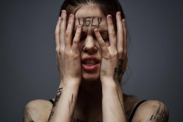 Vrouw met aanstootgevende inscripties op haar lichaam zichzelf aan te raken met handen benadrukken frustratie