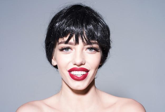 Vrouw met aantrekkelijke rode lippen kijkt naar de camera. mooi glimlachconcept. meisje op blij lachend gezicht poseren met blote schouders.
