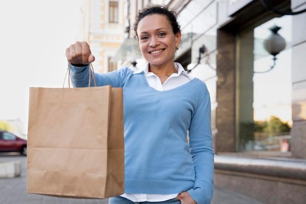 Vrouw met afhaalmaaltijden in papieren zakken