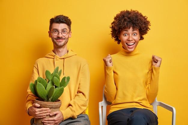 Vrouw met afro-haar balt vuisten voelt zich erg blij viert succes poses op comfortabele stoel in de buurt van vriendje geïsoleerd op geel