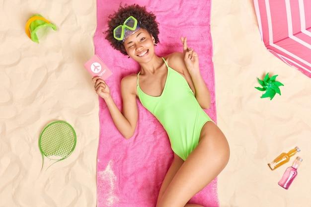 Vrouw met afro-haar heeft paspoort dromen over vakantie in het buitenland houdt vingers gekruist draagt badpak brengt vrije tijd door op het strand met verschillende items in de buurt. zomervakantie