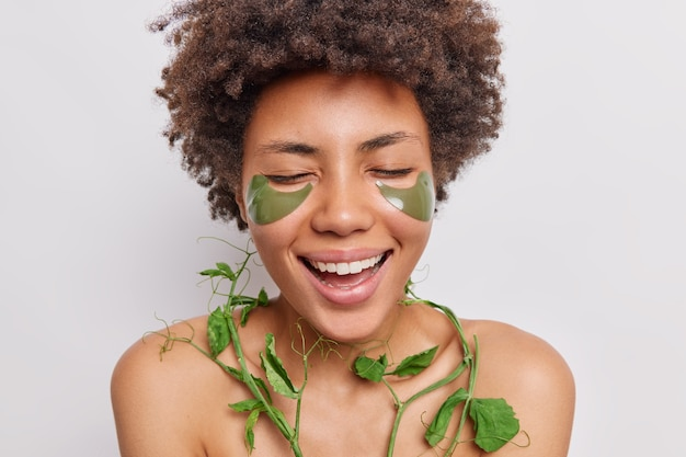 Vrouw met afro-haar lacht positief geniet van schoonheidsprocedures past groene hydrogelpleisters toe onder de ogen gebruikt erwtenpeptiden voor een gladde, zijdezachte huid