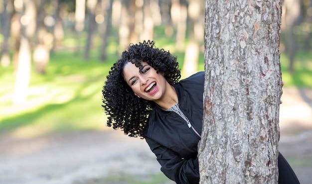 Vrouw met afrohaar, in het bos met plezier gelukkig