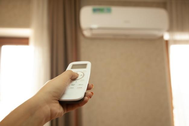 Vrouw met afstandsbediening op airconditioner in de kamer
