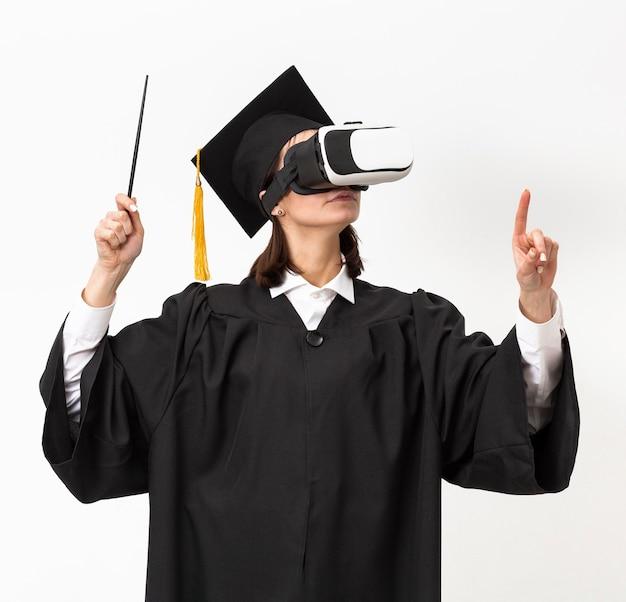 Vrouw met afstuderen gewaad en pet met virtual reality headset