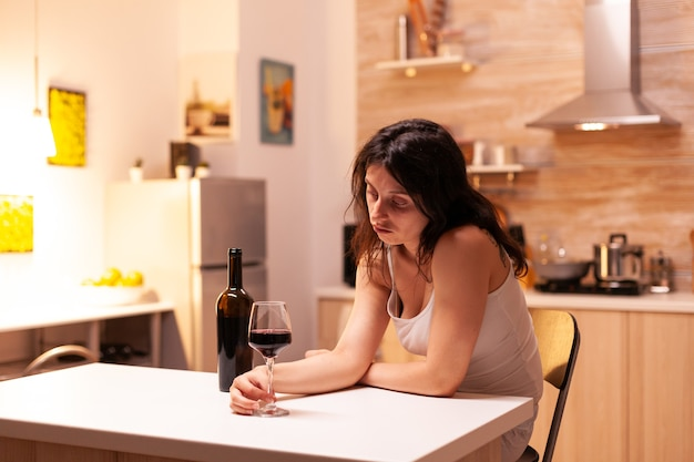 Vrouw met alcoholverslaving en depressie die naar glas met rode wijn kijkt. ongelukkige persoon ziekte en angst gevoel uitgeput met alcoholisme problemen.