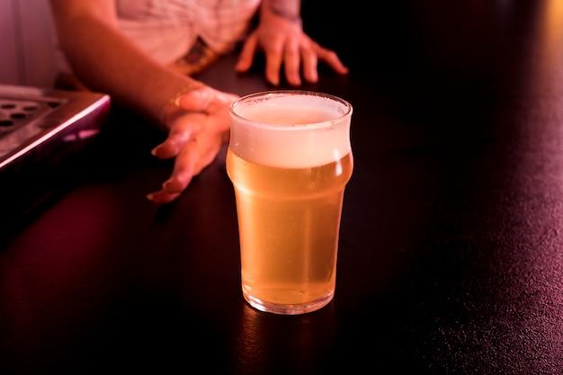Vrouw met ambachtelijke bier in bar