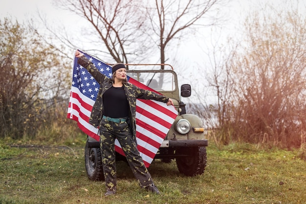 Vrouw met amerikaanse vlag en militaire auto