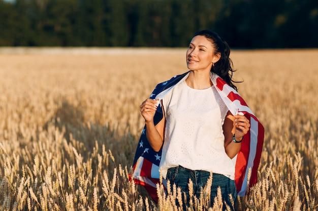 Vrouw met amerikaanse vlag in tarweveld bij zonsondergang. 4 juli. onafhankelijkheidsdag patriottische vakantie.