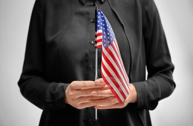 Vrouw met amerikaanse vlag op licht. immigratie naar de vs.