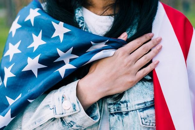 Vrouw met amerikaanse vlag op schouders