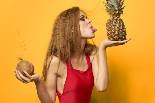 Vrouw met ananas en kokos cocktail exotisch fruit zomer levensstijl geel