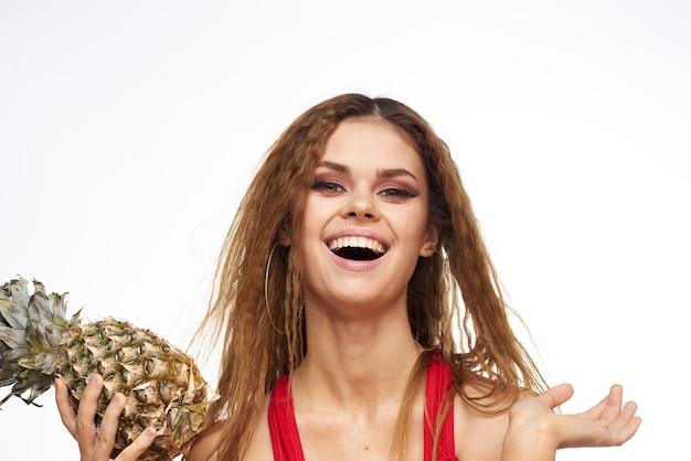 Vrouw met ananas in handen golvend haar rood t-shirt fruit zomervakantie lichte achtergrond.