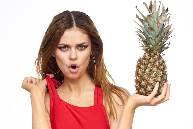 Vrouw met ananas in handen golvend haar rood t-shirt fruit zomervakantie lichte muur.