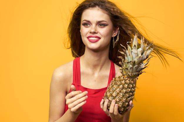 Vrouw met ananas in handen wit t-shirt exotische zomerpret geel