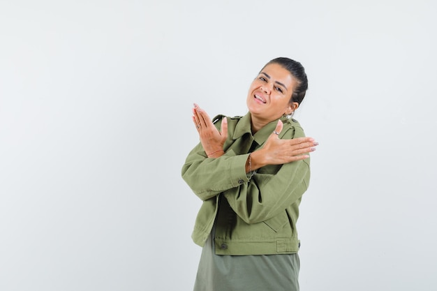 Vrouw met armen gekruist in jas, t-shirt en op zoek zelfverzekerd.