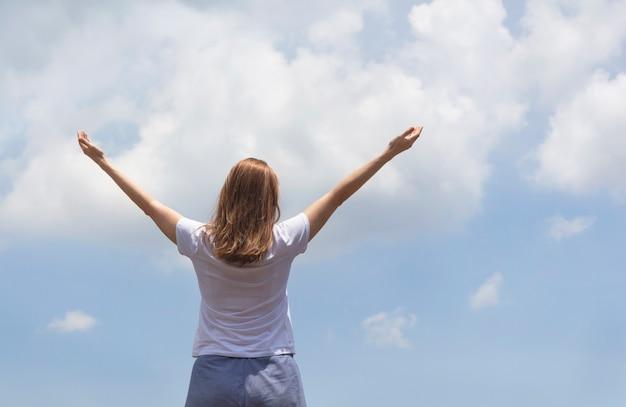 Vrouw met armen omhoog naar de blauwe lucht die vrijheid viert met een foto van hoge kwaliteit