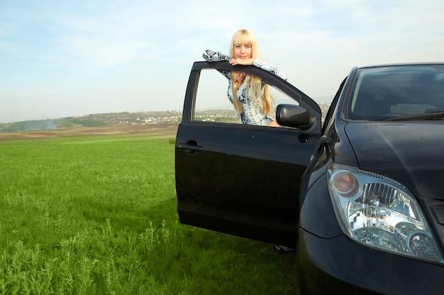 Vrouw met auto in het veld
