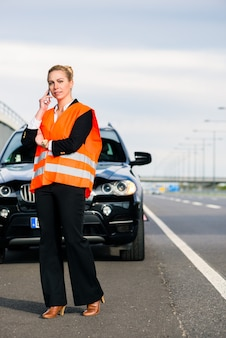 Vrouw met autoanalyse die slepend bedrijf roept