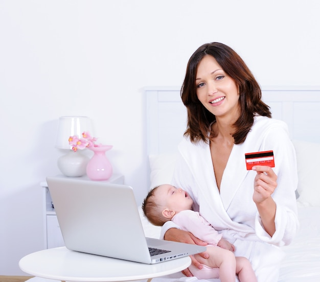 Vrouw met baby, creditcard en laptop thuis