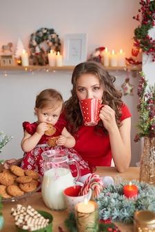 Vrouw met baby in de keuken voor kerstmis wordt verfraaid die.