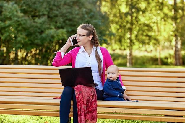 Vrouw met baby telewerkt in park met laptop